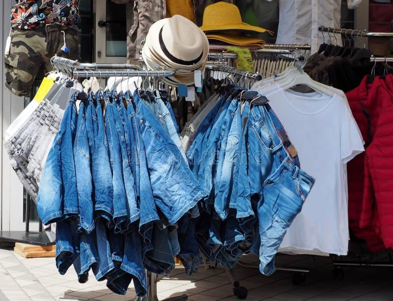 De jeansborrels op een hanger buiten een kleding winkelen gespecialiseerd in de zomermanier stock fotografie