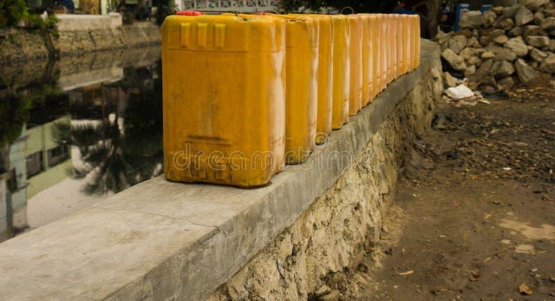 De jerrycans bevindt zich op een rij dichtbij vuile die rivierfoto in Djakarta Indonesië wordt genomen stock afbeelding