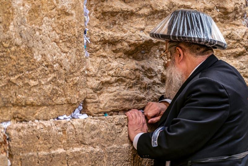 11/23/2018 de Jerusalém, Israel, judeu de crença está rezando perto da parede do grito em um chapéu negro grande em um raincover fotos de stock