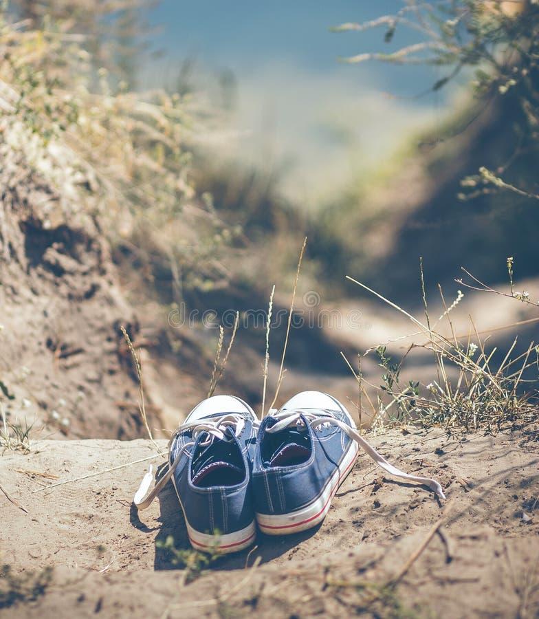 De jeugd blauwe tennisschoenen ter wereld stock foto