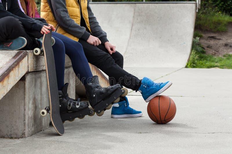 De jeugd brengt vrije tijd bij een skatepark door stock fotografie