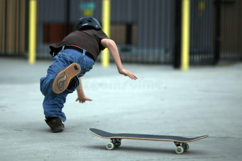 De jeugd die van Skateboard valt stock foto