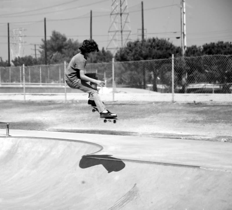 De jeugd die in Zwart-wit met een skateboard rijdt stock foto's