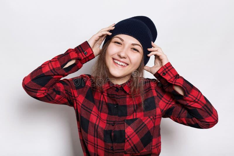 De jeugd en gelukconcept Mooie tiener die modieus gelukkig en GLB en rood gecontroleerd overhemd dragen die houdend haar han zijn stock foto