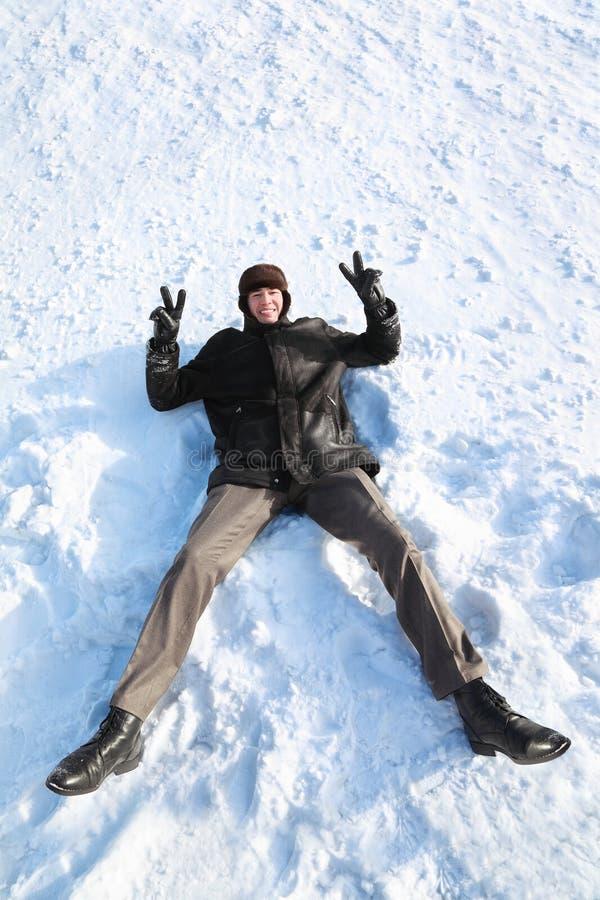 De jeugd ligt op sneeuw op rug en toont handengebaar royalty-vrije stock afbeeldingen