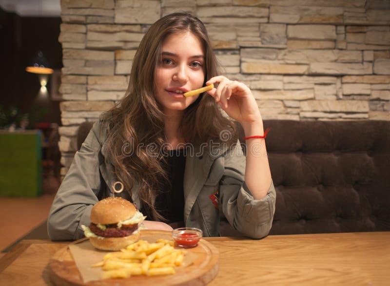 De jeugd mooi meisje die in koffie snel voedsel eten stock afbeelding