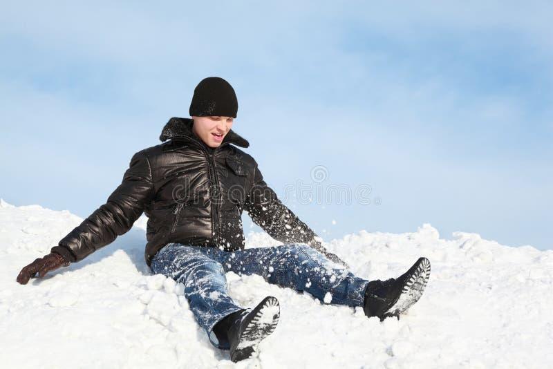 De jeugd zit op sneeuw en werpt omhoog hem stock foto's