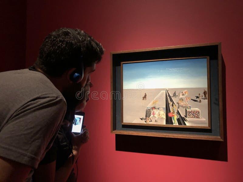 De de jeugdman en de de jeugdvrouw bekijken het beroemde het schilderen art. stock foto
