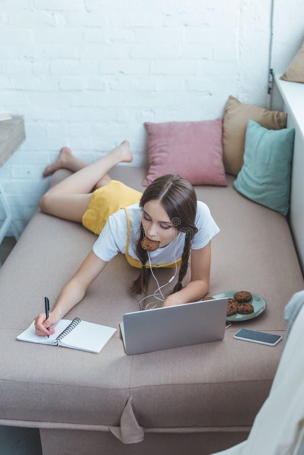 de jeugdstudent met koekjes gebruikend laptop en schrijvend in voorbeeldenboek terwijl het liggen op bank stock foto