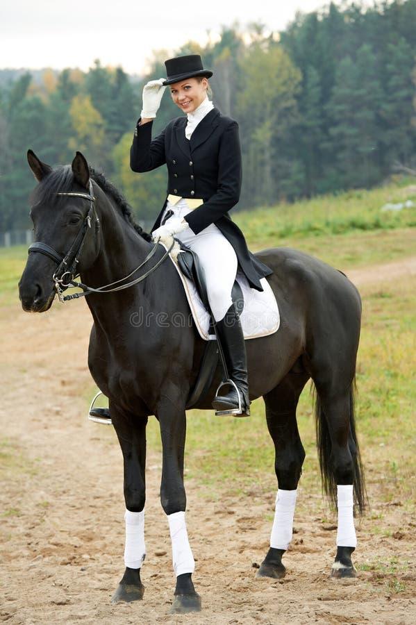 De jockey van de amazone in eenvormig met paard stock fotografie