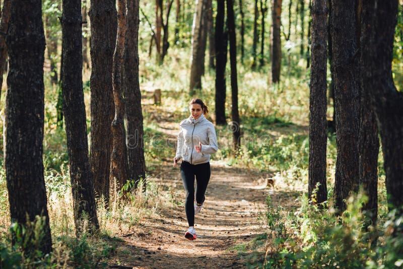 De jogging van de agentvrouw in de herfstpark royalty-vrije stock afbeelding
