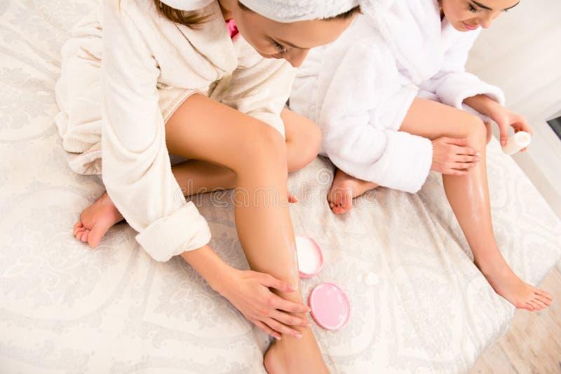 De jolies jeunes femmes se frottant les jambes avec de la crème images stock