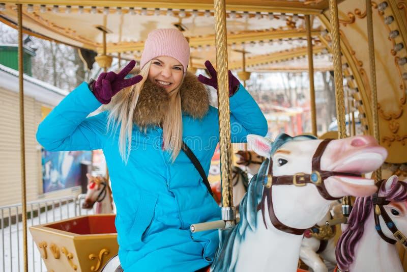 De jonge aanbiddelijke blondevrouw geniet van de de wintervakantie op de carrousel die van het stadspark v-gebaar doen Levensstij stock foto's