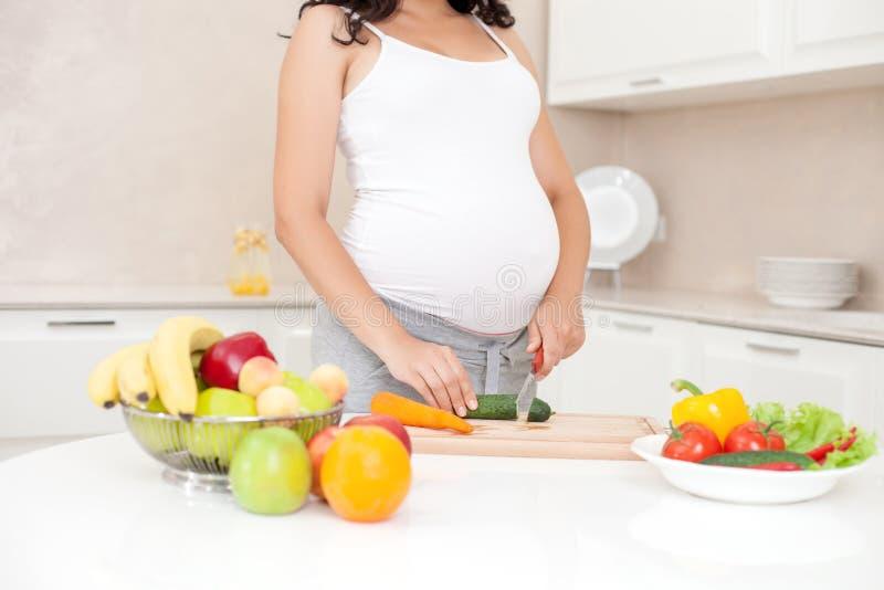 De jonge aanstaande moeder kookt gezond voedsel royalty-vrije stock foto's
