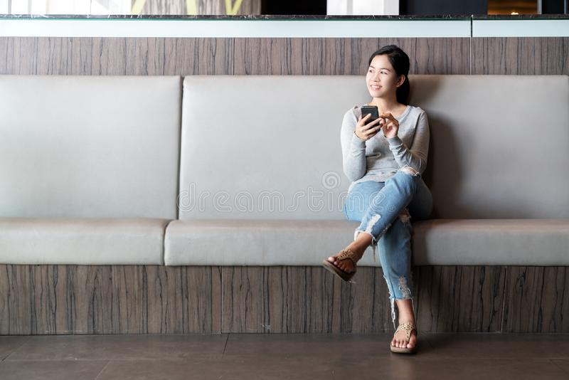 De jonge aantrekkelijke Aziatische vrouw die dwarsbeen zitten bij laagbank die smartphone gebruiken die het positieve koelen voel stock foto