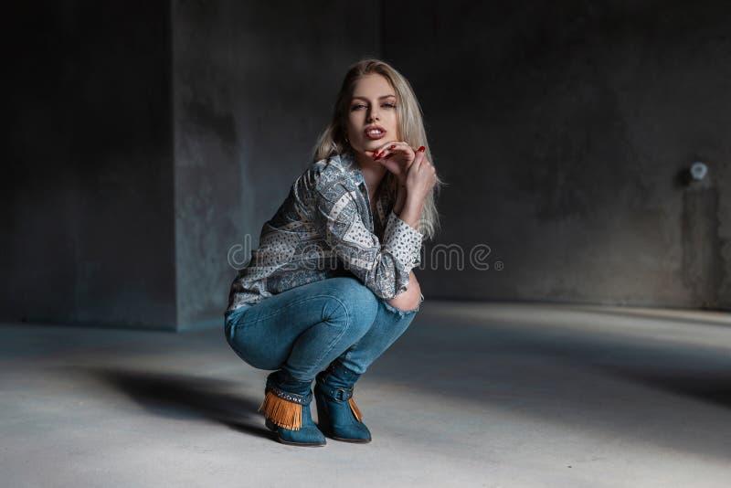 De jonge aantrekkelijke blonde vrouw in modieuze groene cowboylaarzen in een uitstekend overhemd in modieuze gescheurde jeans zit royalty-vrije stock foto