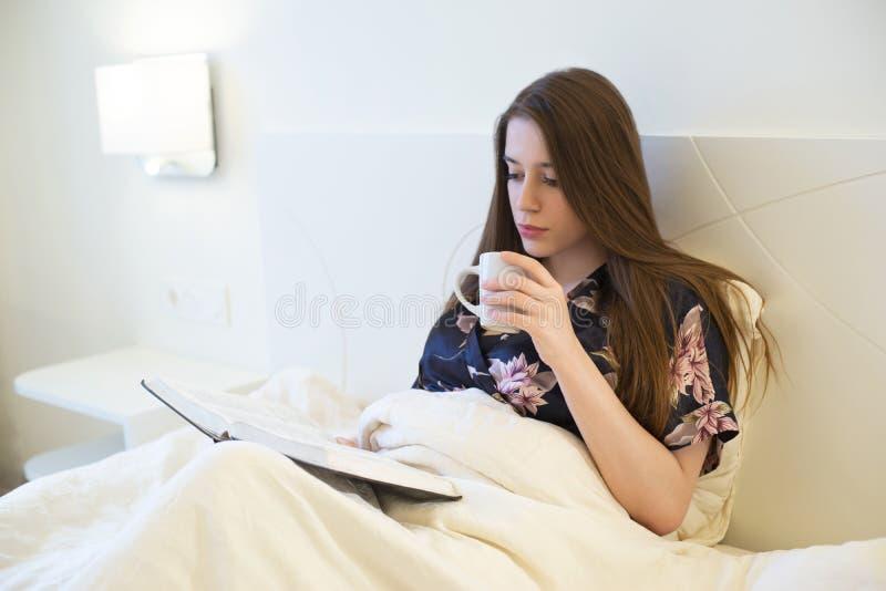 De jonge aantrekkelijke donkerbruine vrouw die in bed liggen die de holdingskop van de zijdepeignoir van offee en lezing dragen b royalty-vrije stock afbeelding