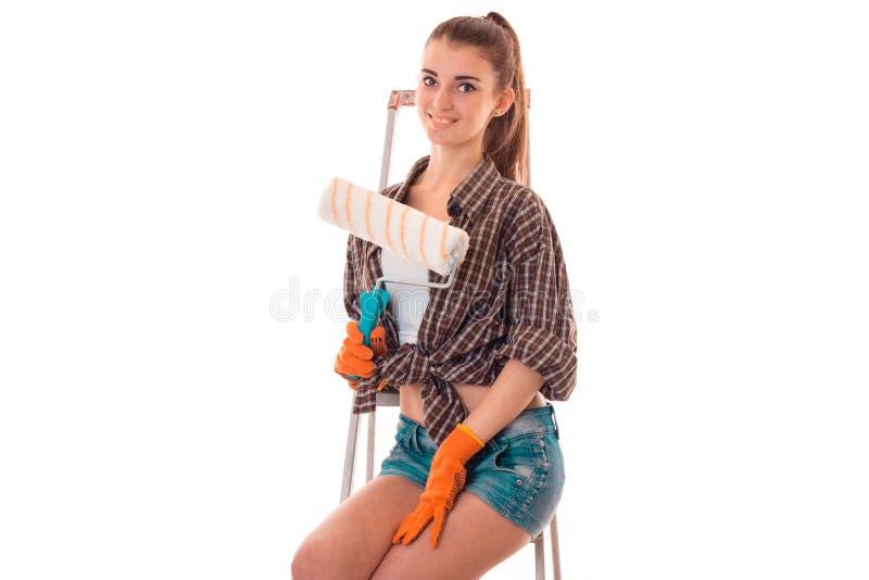 De jonge aantrekkelijke donkerbruine vrouwenbouwer in eenvormig met verfrol in haar die handen maakt reovations op wit wordt geïs stock foto's