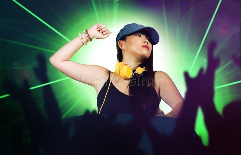 De jonge aantrekkelijke en gelukkige Aziatische Japanse vrouw die van DJ gebruikend deejay toestel en hoofdtelefoons bij nachtclu royalty-vrije stock afbeeldingen