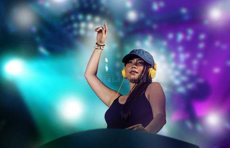 De jonge aantrekkelijke en gelukkige Aziatische Japanse vrouw die van DJ gebruikend deejay toestel en hoofdtelefoons bij nachtclu stock afbeelding
