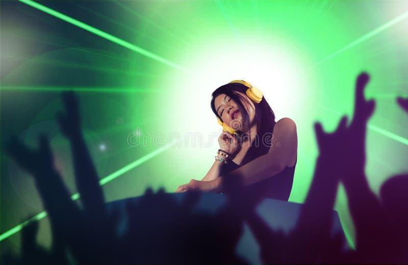 De jonge aantrekkelijke en gelukkige Aziatische Japanse vrouw die van DJ gebruikend deejay toestel en hoofdtelefoons bij nachtclu stock foto
