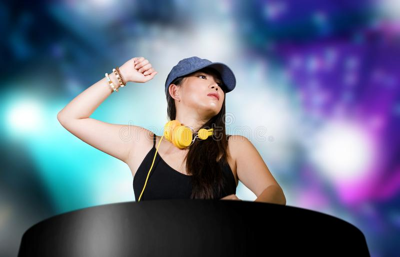 De jonge aantrekkelijke en gelukkige Aziatische Japanse vrouw die van DJ gebruikend deejay toestel en hoofdtelefoons bij nachtclu royalty-vrije stock foto's