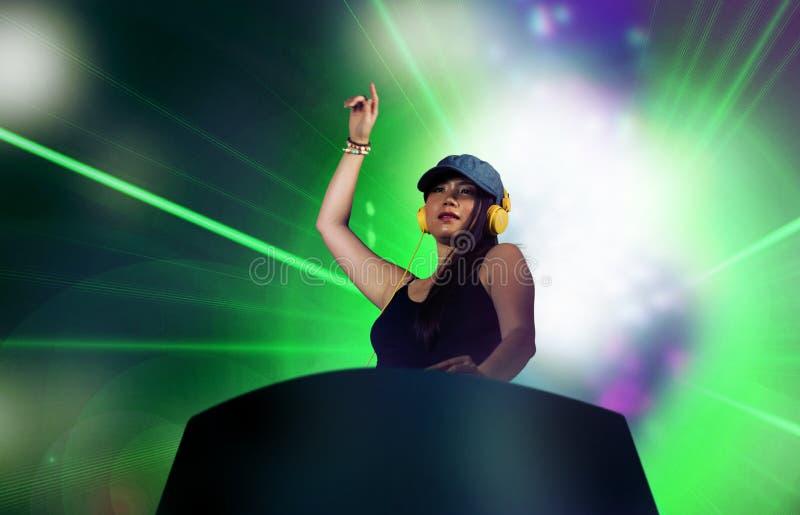 De jonge aantrekkelijke en gelukkige Aziatische Koreaanse vrouw die van DJ gebruikend deejay toestel en hoofdtelefoons bij nachtc stock foto