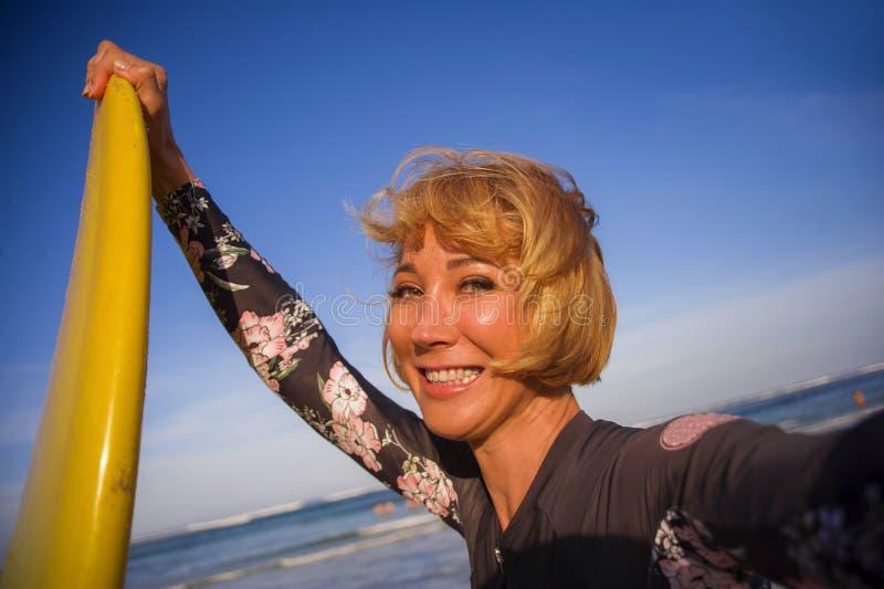 De jonge aantrekkelijke en gelukkige vrouw van de blondesurfer in de brandingsraad van de zwempakholding in het strand die zelfpo royalty-vrije stock fotografie