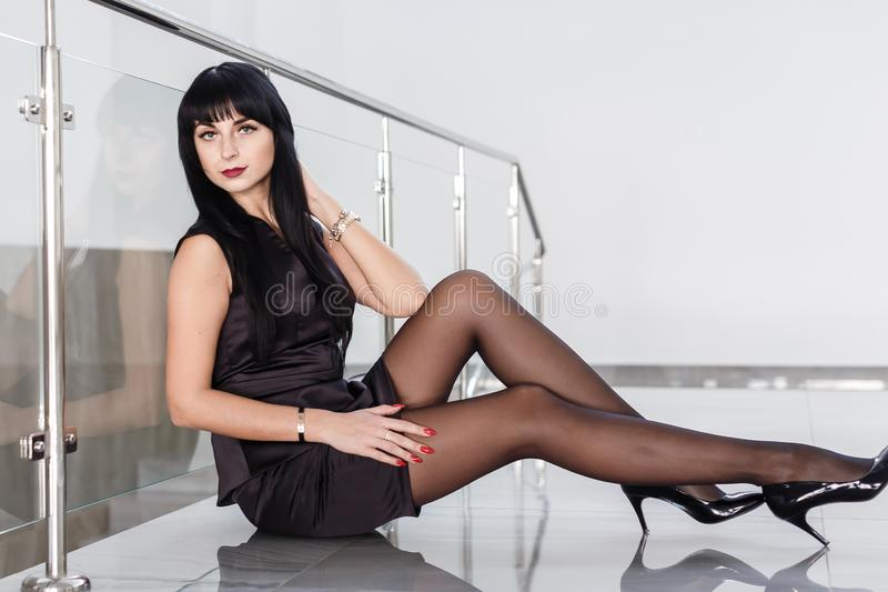 De jonge aantrekkelijke ernstige vrouw gekleed in een zwart pak met een korte rok zit op de vloer in een wit bureau royalty-vrije stock afbeeldingen
