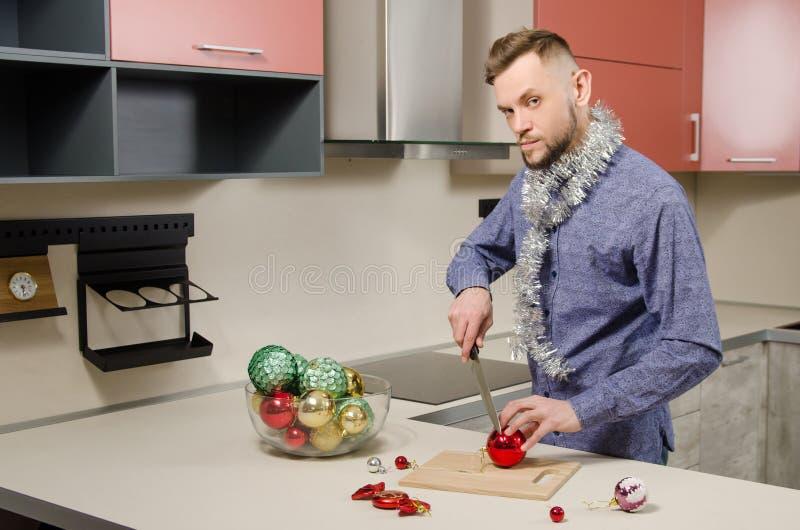 De jonge aantrekkelijke gebaarde mens met mes in zijn hand snijdt salade van verfraaide Kerstmisballen Concept voorbereiding voor royalty-vrije stock foto's