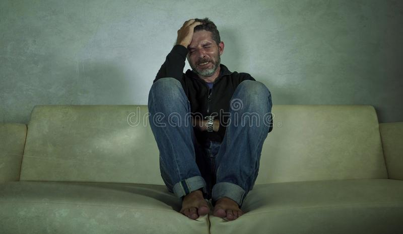 De jonge aantrekkelijke gedeprimeerde en droevige schaduwrijke mens gaat liggen thuis schreeuwen verloren in pijn en wanhoopt lij royalty-vrije stock fotografie