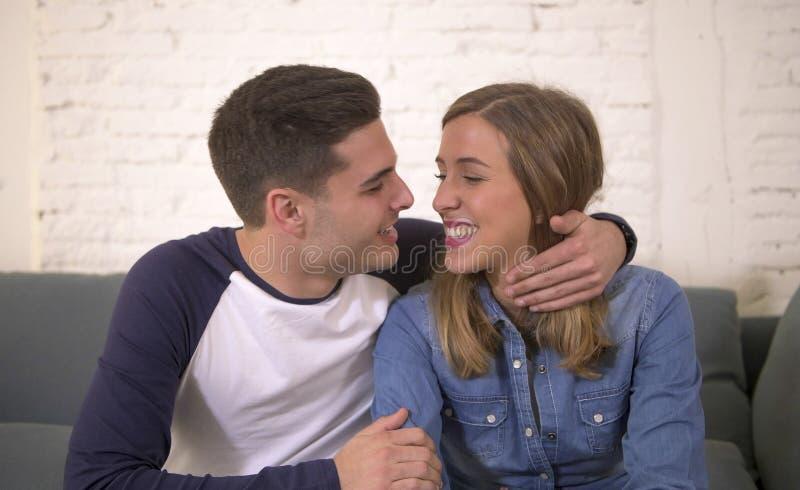 De jonge aantrekkelijke gelukkige en romantische van het paarvriend en meisje knuffelofferte gaat liggen thuis glimlachen speels  royalty-vrije stock foto's