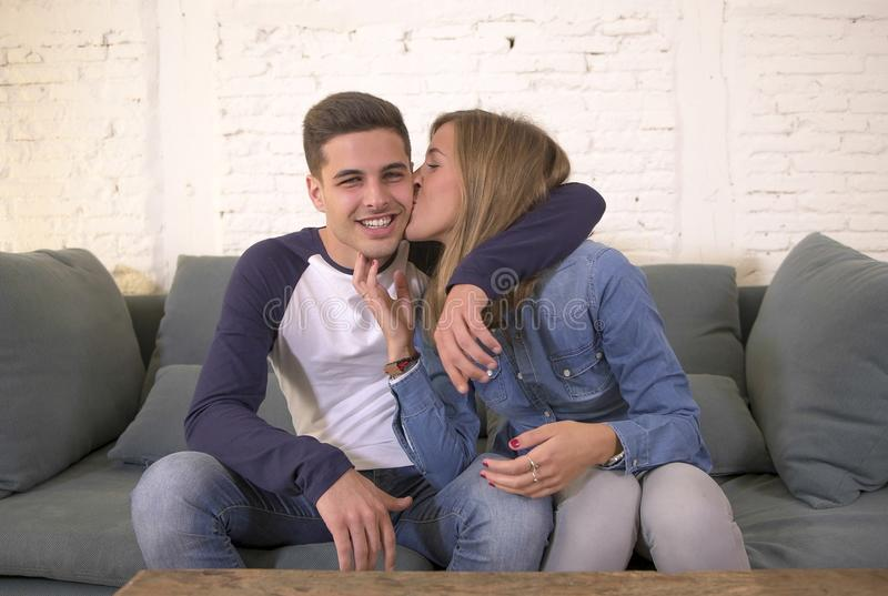 De jonge aantrekkelijke gelukkige en romantische van het paarvriend en meisje knuffelofferte gaat liggen thuis glimlachen speels  stock afbeelding
