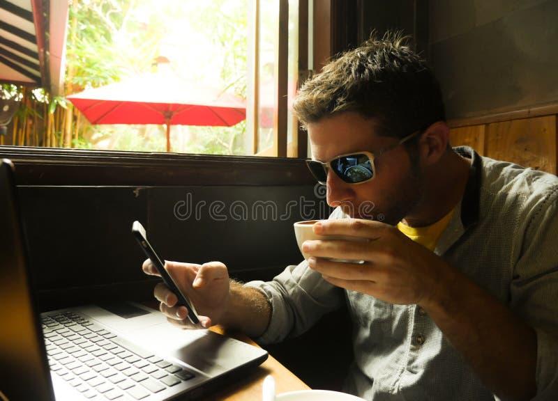 De jonge aantrekkelijke gelukkige en succesvolle millennial mens die van Internet-koffiewinkel werken met laptop computer en mobi royalty-vrije stock foto's