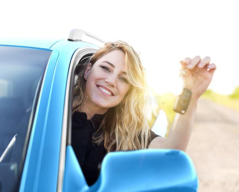 De jonge aantrekkelijke gelukkige vrouw toont sleutels van de nieuwe auto stock foto's