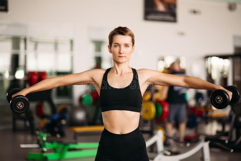 De jonge aantrekkelijke geschiktheidsmeisje het opheffen domorengewichten op rijs dient gymnastiek in royalty-vrije stock afbeelding