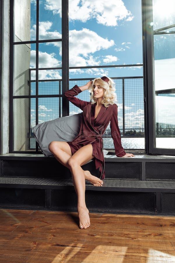 De jonge aantrekkelijke glimlachende vrouw in een zijdepyjama's van Bourgondië zit dichtbij een venster royalty-vrije stock afbeelding