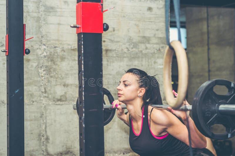 De jonge aantrekkelijke hurkende training van het geschiktheidsmeisje voor benenspieren met barbellgewicht in de gymnastiek, echt royalty-vrije stock foto