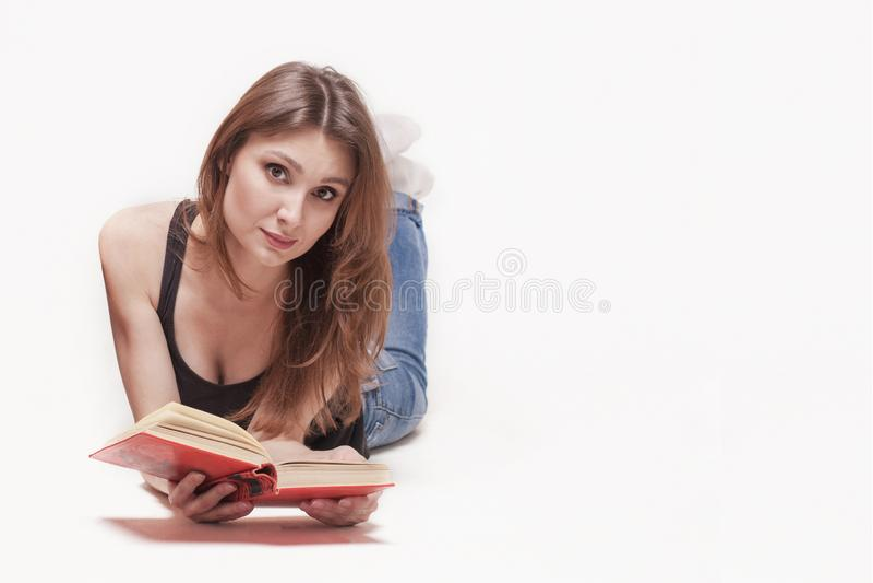 De jonge aantrekkelijke Kaukasische vrouw legt omhoog op de vloerbenen, boek met rode dekking in de handen, lichtjes glimlach Bru stock afbeeldingen