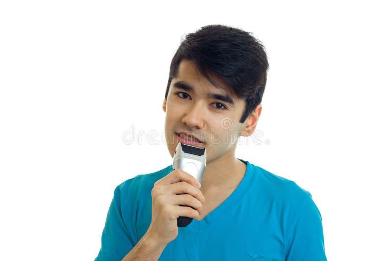 De jonge aantrekkelijke kerel in het blauwe overhemd scheert zijn baard het scheren machine royalty-vrije stock foto