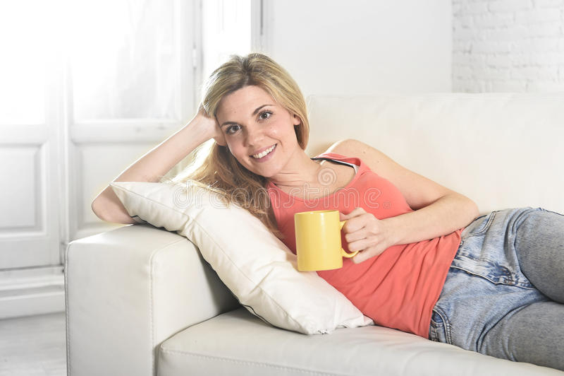 De jonge aantrekkelijke kop van de vrouwenholding van koffiezitting bij banklaag thuis gelukkig glimlachen stock afbeeldingen