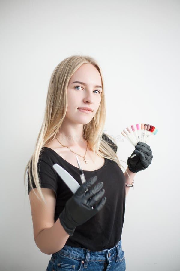 De jonge aantrekkelijke manicure professionele meester van manicurevrouw in een zwarte de rubberhandschoenen is houdt hulpmiddele stock foto