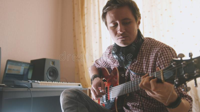 De jonge aantrekkelijke mannelijke musicus stelt en registreert sound-track samen spelend de gitaar gebruikend computer, nadruk o royalty-vrije stock afbeeldingen