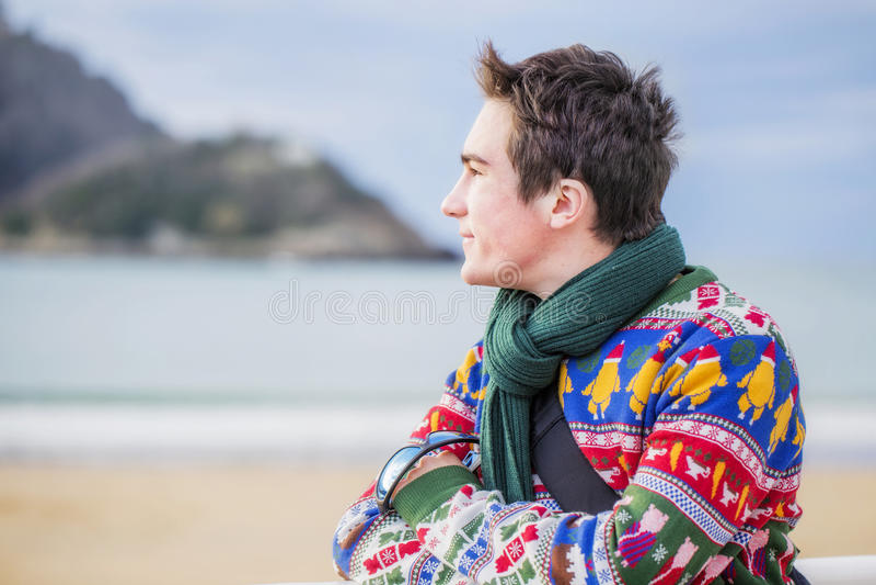 De jonge aantrekkelijke mens die zich op de kust bevinden en bekijkt het overzees royalty-vrije stock fotografie