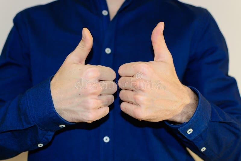 De jonge aantrekkelijke mens, gekleed in het blauwe overhemd tonen beduimelt omhoog royalty-vrije stock afbeelding