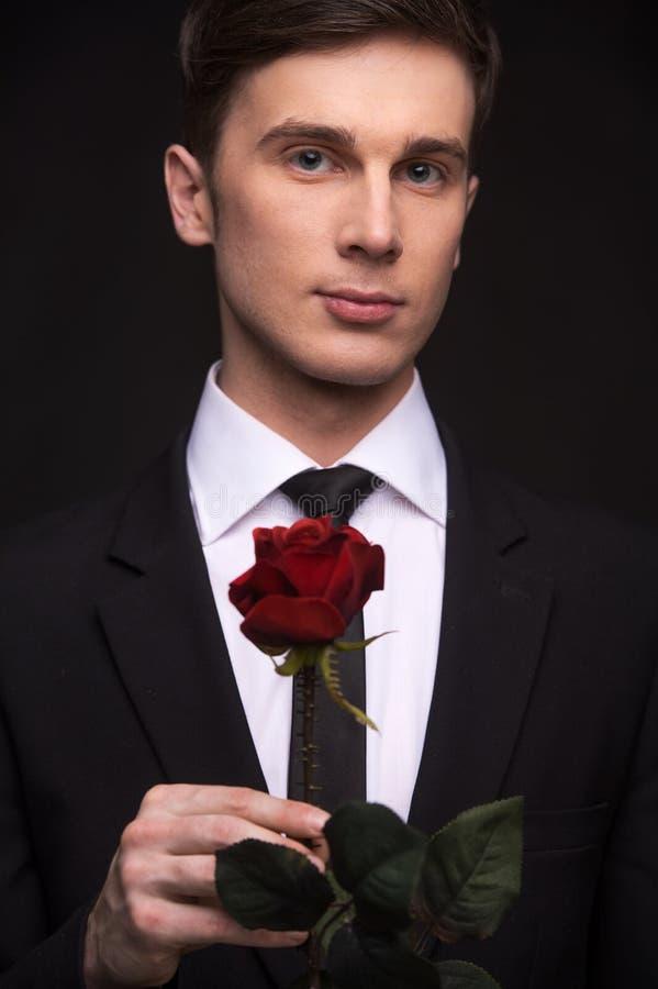 De jonge aantrekkelijke mens in kostuum die rood nam houden toe stock foto's