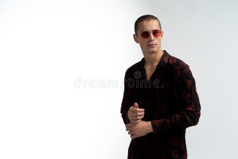 De jonge aantrekkelijke mens met kort kapsel, die rode zonnebril dragen, maakt overhemden leeves, copyspace voor uw tekst recht stock afbeeldingen