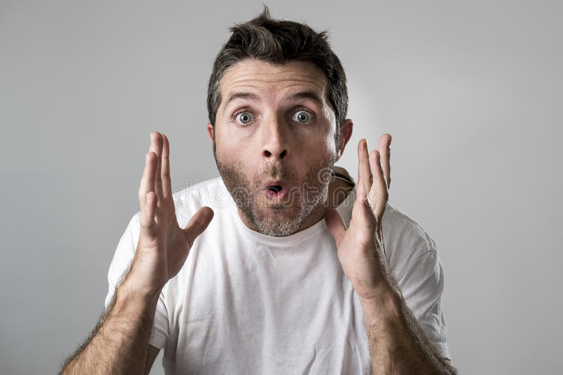 De jonge aantrekkelijke mens verbaasde zich verbaasd in het gezichtsuitdrukking van de schokverrassing en schokemotie stock foto's