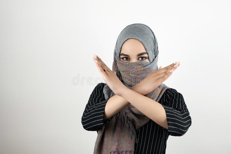 De jonge aantrekkelijke Moslimstudent die tulband dragen die hijab headscarf nr zeggen aan oorlog en geweld houdt haar wapens gek stock fotografie