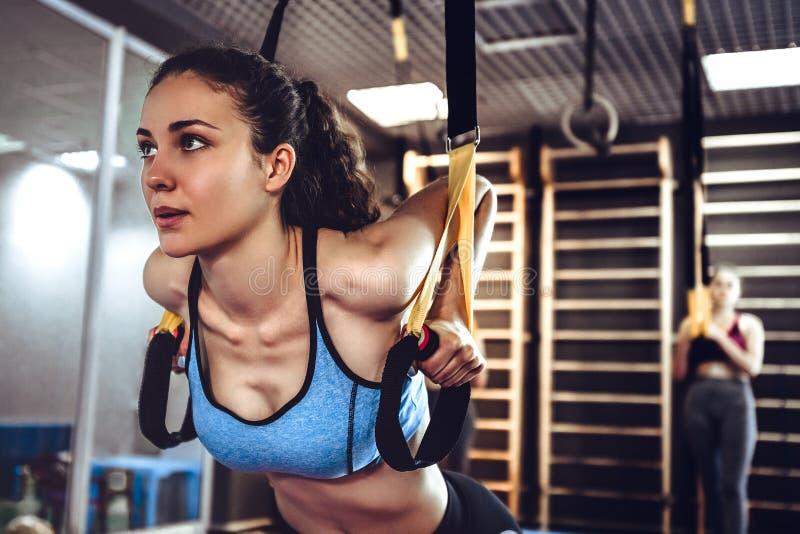 De jonge aantrekkelijke vrouw boort abs schuine opleiding met geschiktheidsriemen in uit de studio van de gymnastiek stock afbeeldingen
